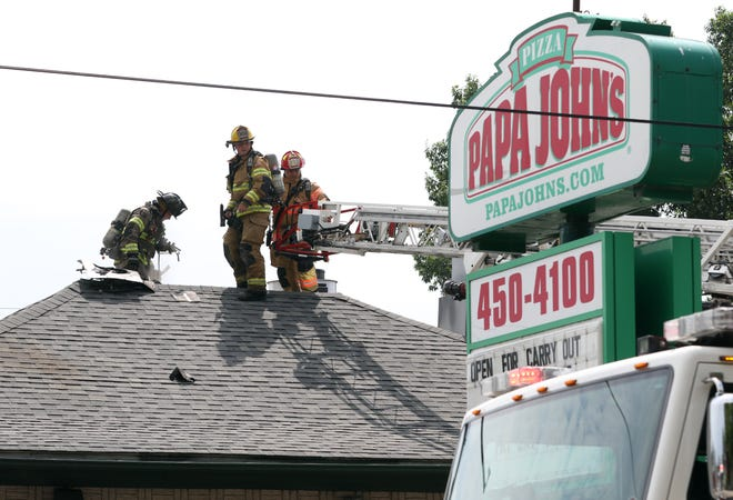 Zanesville Fire Department and Falls Township Fire Department firefighters work on the roof of Pappa John's Pizza on Maple Avenue on Thursday. Fire damaged the pizzaria's exhaust system. No injuries were reported.