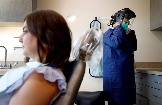 Caring Smiles Family Dentistry dental hygienist Adrienne Vasquez puts on her personal protective equipment before seeing patient Jenny Grondin on June 30, 2020, in West Bloomfield, Michigan. In addition to gowns, the dentists and other staff members are also wearing head gear that protects their faces and adds a different layer of protection. The West Bloomfield practice also has patients fill out a COVID-19 questionnaire and have their temperatures taken before they can be seen.