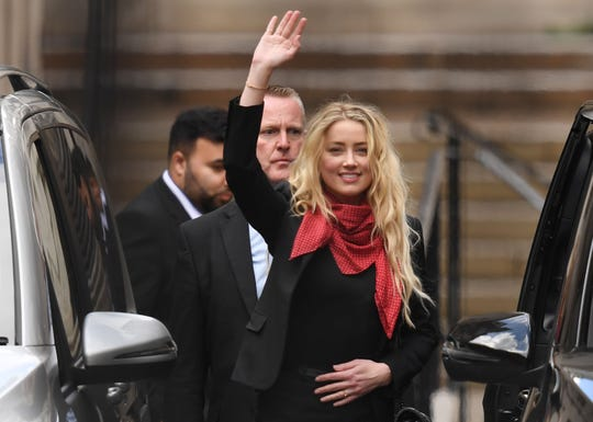 Amber Heard waves as she leaves court in London on July 16, 2020, after day eight of trial in the libel suit filed by her ex-husband Johnny Depp against The Sun tabloid.