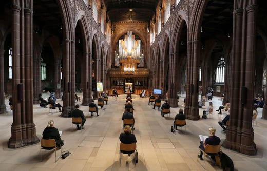 Attendees are sat socially distanced as Bishop of Manchester David Walker (C) leads a memorial service for the victims of the novel coronavirus at Manchester Cathedral in Manchester, northwest England, on July 16, 2020.