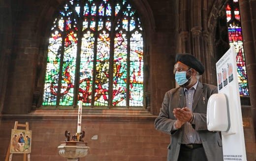 An attendee sanitizes his hands before a memorial service for the victims of the novel coronavirus at Manchester Cathedral in Manchester, northwest England, on July 16, 2020.