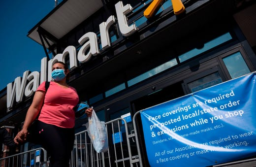 A woman wearing a facemask walks past a sign informing customers that face coverings are required in front of a Walmart store in Washington, DC on July 15, 2020. Walmart will require shoppers to wear face masks starting next week, the US retail giant announced on July 15, joining an increasing number of businesses in mandating the protection amid the latest spike in coronavirus cases.