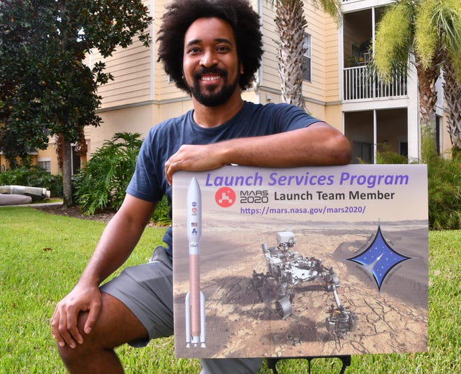 NASA's Launch Services Program posted 450 signs in yards of employees and contractors supporting the upcoming Mars 2020 Mission. Phillip Hargrove, a launch vehicle trajectory analyst for NASA poses with his sign at his apartment complex in Titusville.