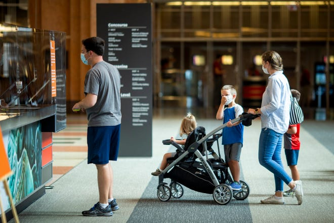 A family enters the Cincinnati Museum Center as it reopens to the public, after being closed for four months due to COVID-19, on Friday, July 17, 2020.