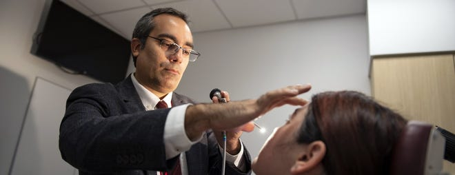 Dr. Ahmad Sedaghat looks into the nasal passage of a patient. Sedaghat is associate professor of otolaryngology and director of rhinology, allergy and anterior skull base surgery at the University of Cincinnati College of Medicine.
