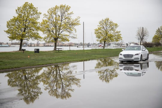 A car drives across standing water near Belle Isle Beach in Detroit May 2, 2019.