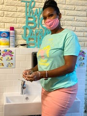LaShawn Bridges washes her hands at a newly installed sink at her child care center in Detroit.