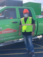 Armando Negron, 56, stands next to a Servpro truck, while in Michigan helping with flood cleanup in the Midland area.  Negron was one of about 200 workers who came to Michigan in late May and early June, after a flood to help clean up buildings, including a hospital, MidMichigan Medical Center - Midland. Servpro subcontracted with BTN, a Texas company. He and other workers said their safety was ignored and as a result, got infected with the coronavirus. He is now back at home in Florida recovering.