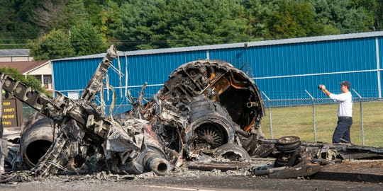 A member of the National Transportation Safety Board looks at the wreckage of a plane that Dale Earnhardt Jr., his wife and daughter and two pilots and a dog were on when it crash landed Thursday at the Elizabethton Municipal Airport in Elizabethton, Tenn., Friday, Aug. 16, 2019.