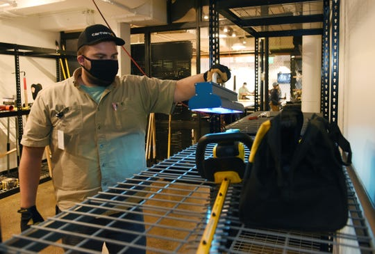 Carhartt employee Miguel Mereles uses UV light to sanitize equipment at its tool-lending department in Detroit.