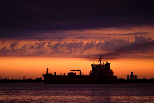 The freighter Algoterra moves up the Detroit River against a vibrant sunrise near Wyandotte in this June 27, 2019, file photo.
