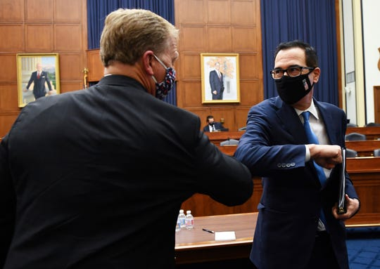 Treasury Secretary Steven Mnuchin, right, elbow bumps with Rep, Kevin Hern, R-Okla., after a House Small Business Committee hearing on oversight of the Small Business Administration and Department of Treasury pandemic programs Friday on Capitol Hill in Washington.