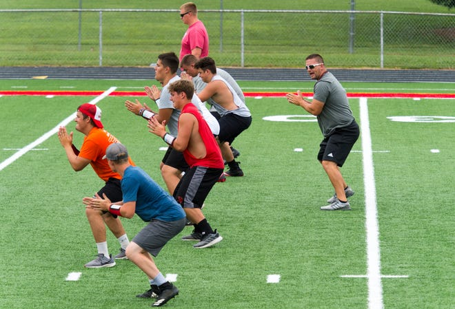 Players guided by head coach Waylon Schenk, right, work on offensive line posture drills during football practice at North Posey High School Thursday morning, July 16, 2020.