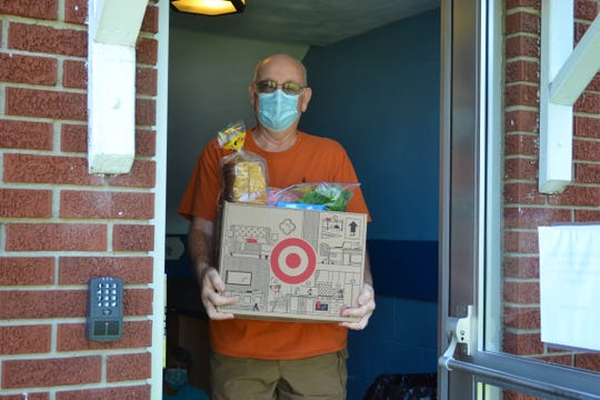 Volunteer Bob Savage carries a box full of food to a waiting family at Elmore Church of God. Over 43 children receive free breakfasts and lunches each week. The church welcomes monetary and food donations to help support the program.