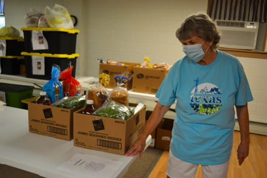 Volunteer Linda Savage stands next to boxes of food as she talks about the free breakfast and lunch program at Elmore Church of God. Linda and her husband Bob are two of the many people who volunteer their time to the program each week.
