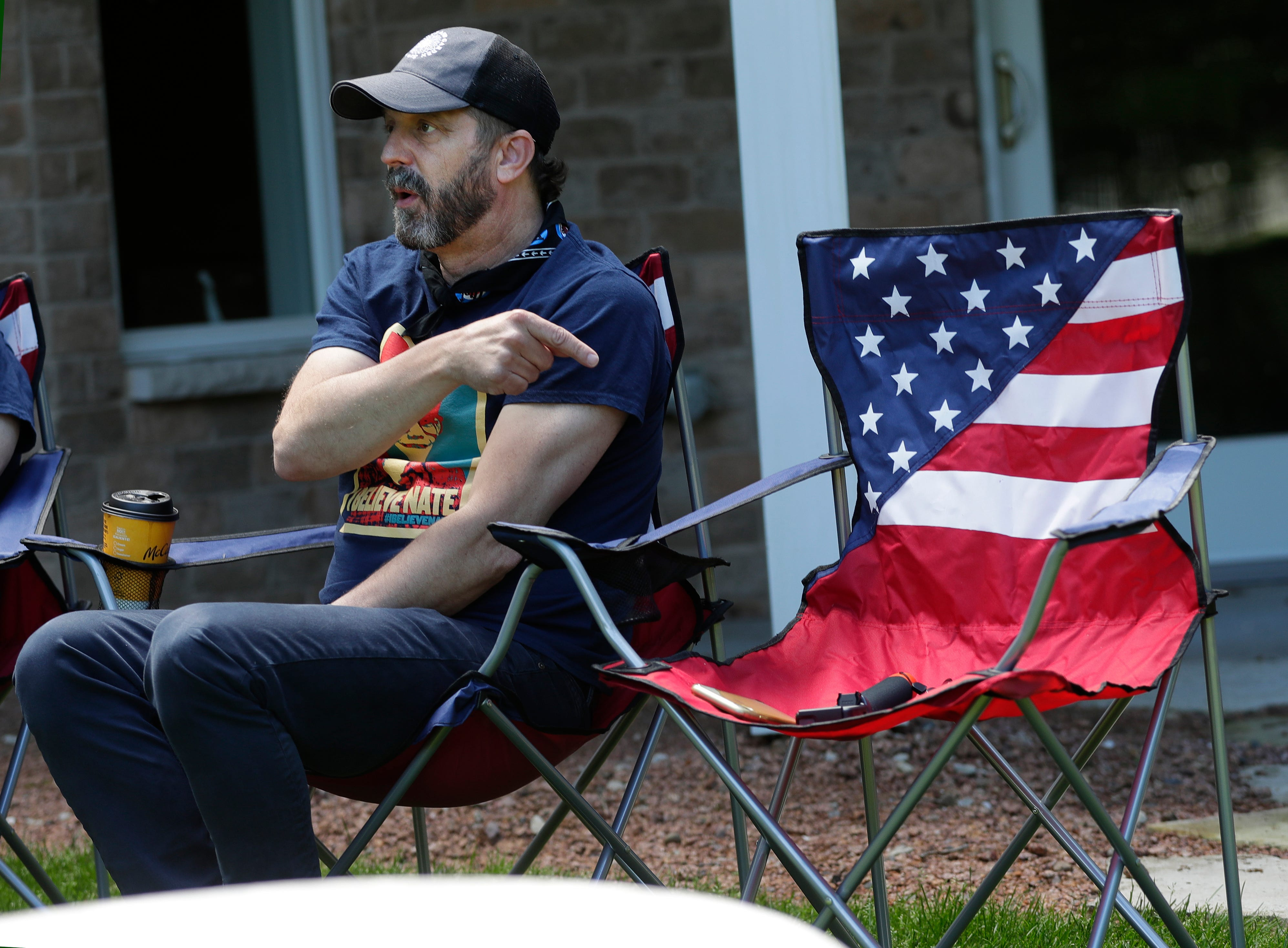Aaron Lindstrom points to an empty chair in his parents' backyard in Hobart, Wis. on June 6, 2020, while saying his brother, Nate, could have been sitting there. Nate Lindstrom, 45, said three priests sexually abused him as a teen; he died by suicide in March 2020.