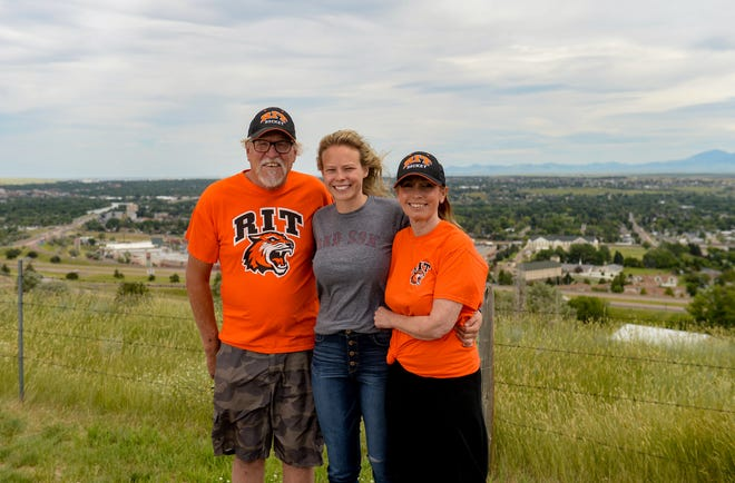 Celeste Brown poses with her parents Mike and Carol Brown at a city overlook near the Great Falls International Airport as they see her off after she accepted the head coaching job of the women's hockey program at Rochester Institute of Technology in New York state.  Celeste Brown, a Great Falls native, was officially named the head coach of RIT women's hockey on Friday, July 17, 2020.