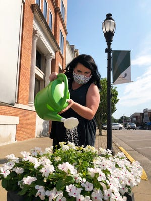 Katie Beth Shelton, a senior relationship banker at Field & Main Bank, waters a large Downtown Henderson Partnership flower pot at the intersection of Second and Main streets on Wednesday. Employees of the bank and its sister insurance agency have volunteered to water three pots seven days a week. Field & Main is one of more than 20 downtown businesses, residents and advocates who have volunteered to keep the 52 DHP flower pots in the central business district watered this summer. (Photo by Chuck Stinnett)