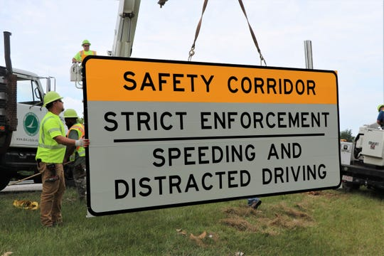 Ohio Department of Transportation workers install new signs along the eastbound lanes of US 33, designating 12 miles of the highway within Fairfield County as a distracted driving safety corridor. The project is a partnership between ODOT and the Ohio State Highway Patrol.