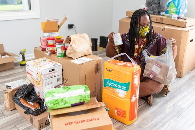 "Shauntrice Martin with Feed the West packages items for delivery in her home. ""We deliver free groceries, supplies, masks and literally anything you can get at a grocery store,"" Martin said. Residents can fill out a form stating the items they are in need of and Martin and volunteers will deliver them, or they may be able to pick them up at locations like the Parkland Boys and Girls Club. July 16, 2020"