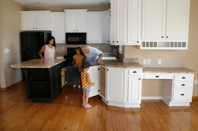 Nick Romano and  Evelyn Romano, with their daughters Isabella, 7, and Gabriela, 3, explore their new home in Oconomowoc.