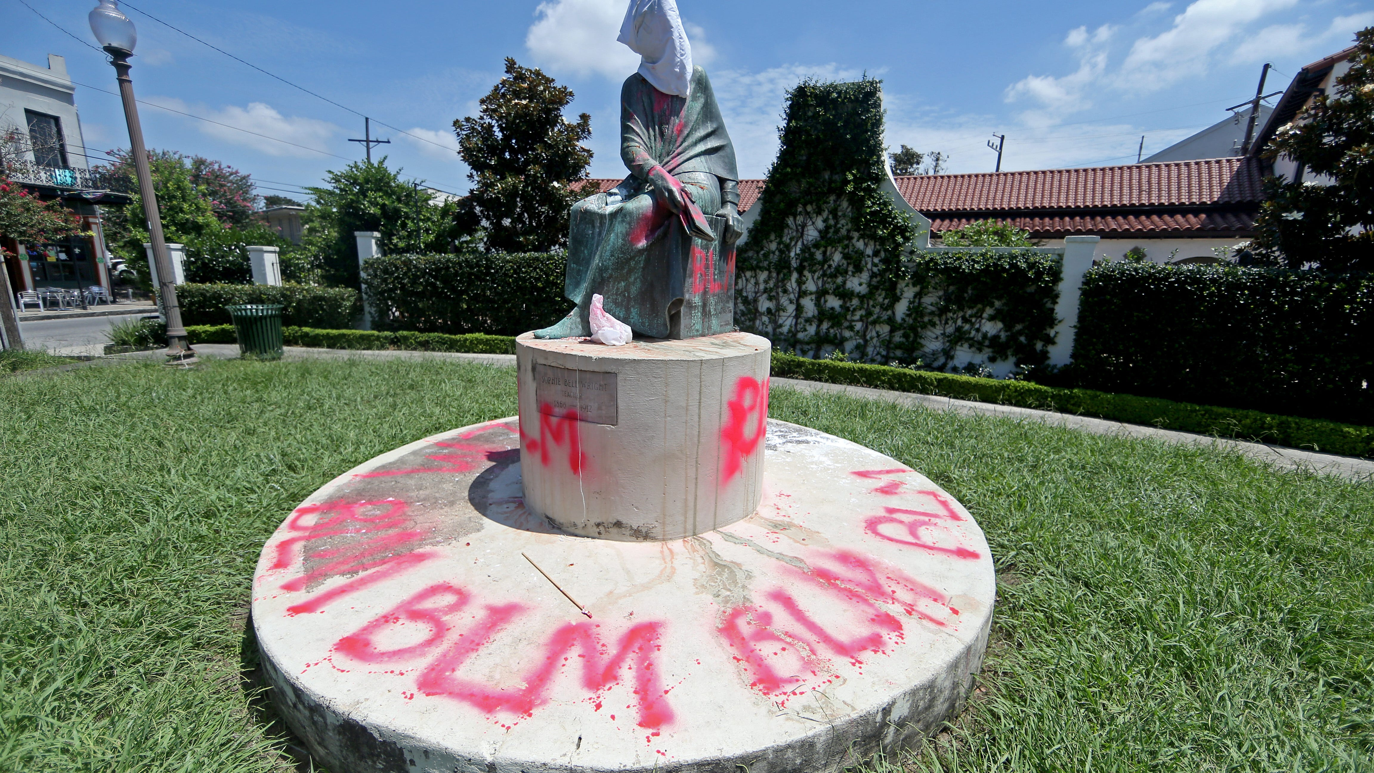 A confederate monument with graffiti and a sack over the statue's head