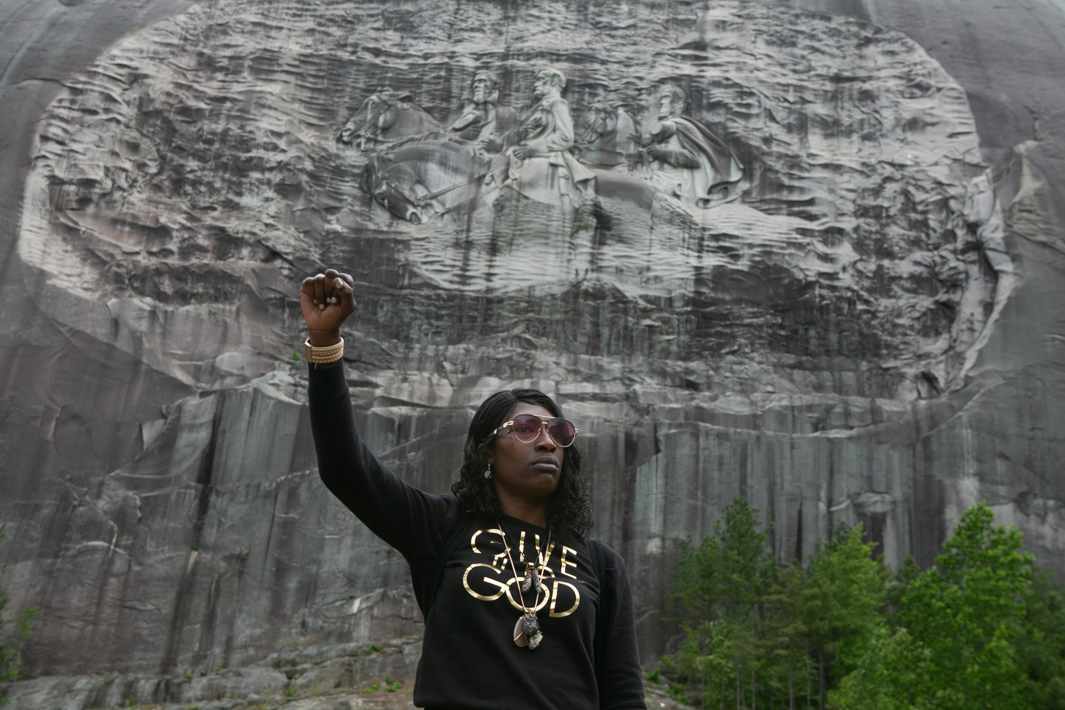 STONE MOUNTAIN, GA - JUNE 16: Lahahuia Hanks holds up a fist in front of the Confederate carving at Stone Mountain Park during a Black Lives Matter protest on June 16, 2020 in Stone Mountain, Georgia. The march is to protest confederate monuments and recent police shootings.  Stone Mountain Park features a Confederate memorial carving depicting Stonewall Jackson, Robert E. Lee, and Jefferson Davis, President of the confederate states.  (Photo by Jessica McGowan/Getty Images)