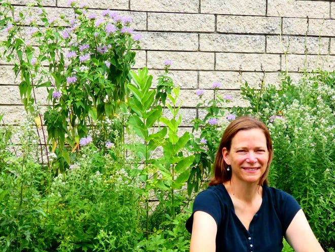 Karen Goodell, a professor at OSU Newark teaching and researching biology, ecology and conservation, poses in front of a collection of native plants outside of Adena Hall on campus.