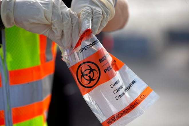 A testing kit is prepared to get a sample from a patient to test for COVID-19 at a federal surge testing site at Maryvale High School in Phoenix, on July 17, 2020.