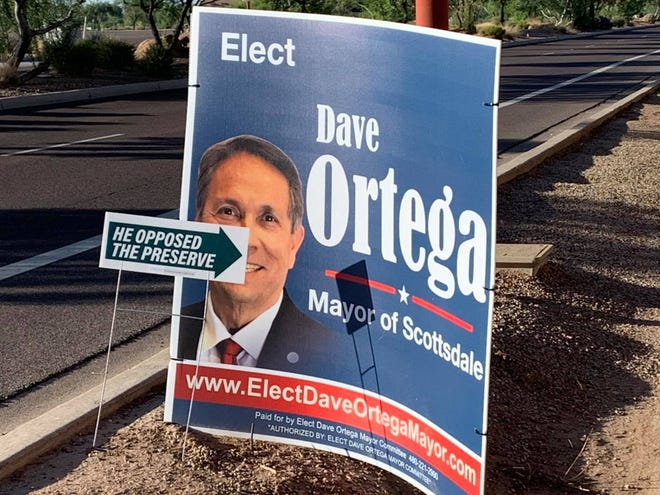 A sign from Rose to Rise PAC in front of a campaign sign for mayoral candidate Dave Ortega. The sign is part of a broader campaign resurfacing Ortega's past opposition to the McDowell Sonoran Preserve.