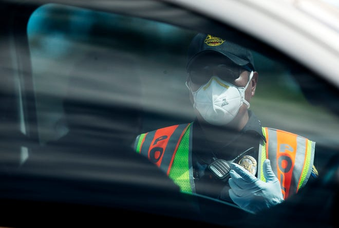 A Phoenix police officer gives information and directs traffic for viral testing for COVID-19 at a federal surge testing site at Maryvale High School in Phoenix, on July 17, 2020. The surge testing site which is free will continue at Maryvale High School for 12 days.