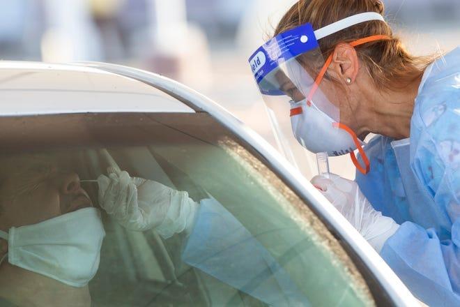 Angelica Topka (der) realiza la prueba para COVID-19 a Julian García, organizado por la Fundación HeroZona en el estacionamiento de South Mountain Community College en Phoenix, Arizona, el 9 de julio de 2020.