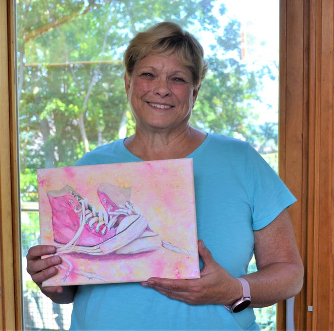 Jan Hackett holds one of her original works in her Port Clinton home studio. Hackett is a retired educator who recently founded The Fine Art Café, a website where artists promote their work and connect with buyers. The website fulfilled Hackett's longtime dream of finding a means to support other artists.