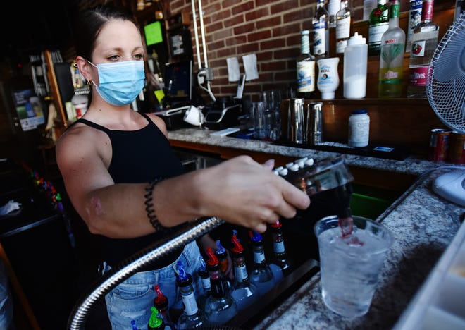 Bartender Kelsey Drozda makes a drink behind the bar at the Riverside Cafe in Wilkes-Barre, Pa., Wednesday, July 15, 2020. To fight the coronavirus, nightclubs will be shut down, bars will be closed unless they also offer dine-in meals, and bars and restaurants will be limited to 25% capacity under Gov. Tom Wolf's order, which takes effect Thursday and also requires companies to have their employees telework to the extent possible. (Sean McKeag/The Citizens' Voice via AP)
