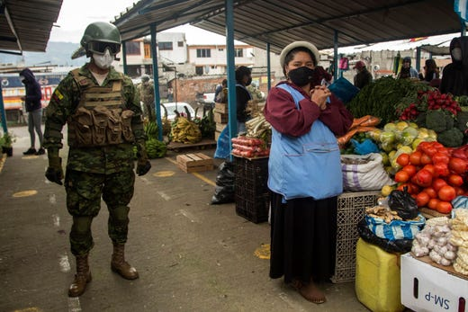 An Ecuadorean soldier patrols a market as part of an inter-institutional operation alongside the National Police and the municipality to enforce lockdown restrictions amid the new coronavirus pandemic at Guamani -a COVID-19 high contagion sector-, in southern Quito, on July 17, 2020.
