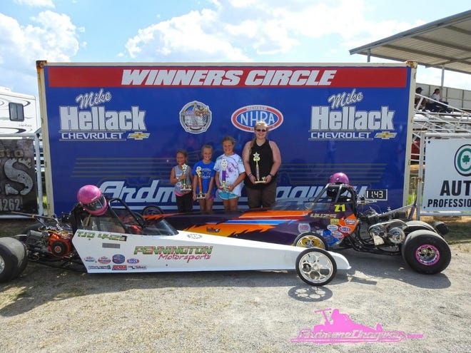Skyler Wright, far right, stand un the winner circle. The recent Plainview grad began drag racing in 2014.