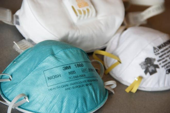 Two N95-type face masks, or respirators, sit in the foreground with an N100-type mask in the background. While cloth face coverings can prevent the spread of a virus, these masks are certified by the National Institute for Occupational Safety and Health to protect against particulates like viruses.