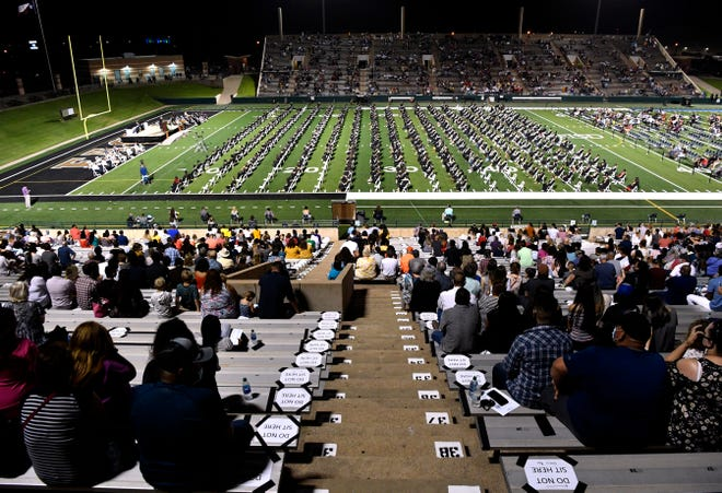 Families and guests watch as Abilene High School holds commencement Friday in Shotwell Stadium. The new location and a more than month-long delay was due to the coronavirus pandemic