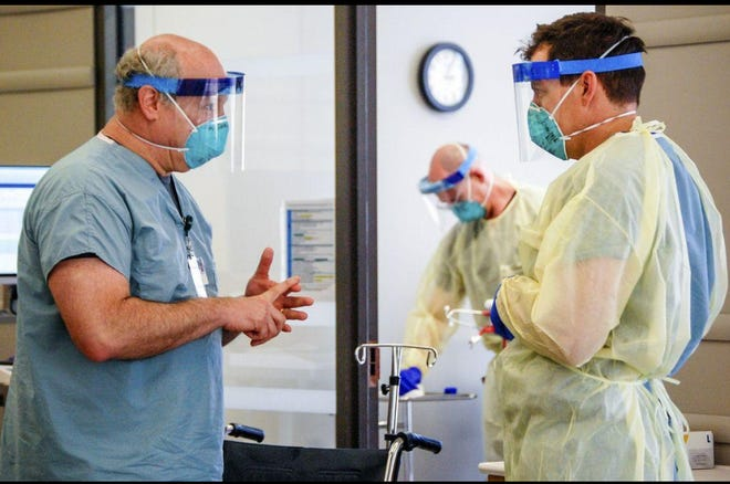 Dr. Michael Saag, left, speaks with an unidentified coworker in Birmingham, Ala., on Friday, July 10, 2020. Saag survived COVID-19 and now treats patients with the disease.