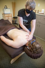 East Village Spa Owner and licensed massage therapist, Cassie Sampson, massages a client.