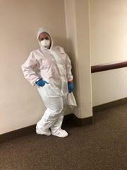 Marali Rubio, 50, of Orlando, Florida, an immigrant from Venezuela, wears a full hazmat suit during a restoration job in California in March. At that job, Rubio said she and other workers were given good safety equipment and regulations, in contrast to Michigan, where they were not given proper equipment while cleaning out buildings such as the hospital, MidMichigan Medical Center - Midland.