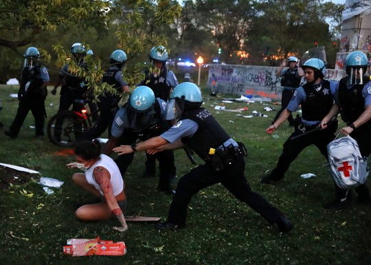 A protester and Chicago police clash after protesters tried to topple the Christopher Columbus statue in Grant Park during a rally calling for the defunding of the CPD on Friday.