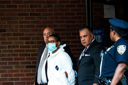 Tyrese Haspil, 21, is escorted out of the 7th precinct by NYPD detectives, Friday in New York.