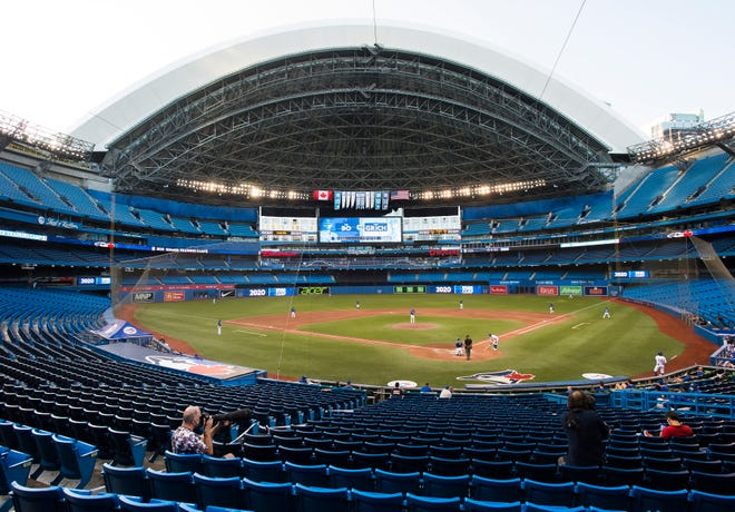 Photographers cover the game Friday in an empty stadium during an intrasquad game in Toronto.
