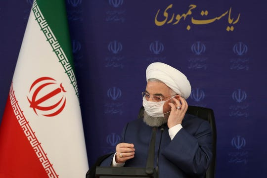 In this photo released by the official website of the office of the Iranian Presidency, President Hassan Rouhani adjusts his face mask in a meeting of the national headquarters of the fight against the COVID-19, in Tehran, Iran, Saturday. He estimated as many as 25 million Iranians could have been infected with the coronavirus since the outbreak's beginning, citing an Iranian Health Ministry study that has so far not been made public, the state-run IRNA news agency reported.