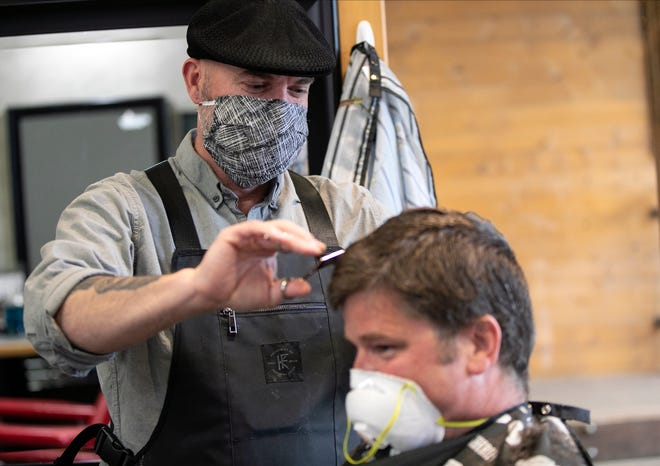 In this July 17, 2020, file photo, co-owner Bryan Kirkland cuts the hair of Mike Fallaw, a typical customer at The Barbershop & Shaving Parlor in Bozeman. Cascade County officials voted Wednesday that the local mask mandate will continue, even if new Gov. Greg Gianforte eases COVID-19 restrictions.