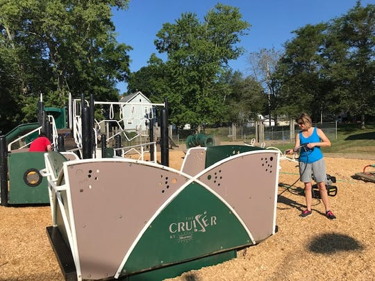 Tammy Hitchman uses a power washer to spuce up the Cruiser at Hitchman Park's new playscape which is handicapped accessible. Lou Whitmire/News Journal