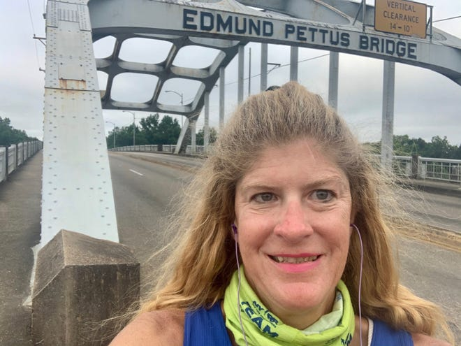 Lori Eidson-Riggles stands at the Edmund Pettus Bridge in Selma, preparing to for her 52.4 mile run into Montgomery on Thursday, July 16, 2020.