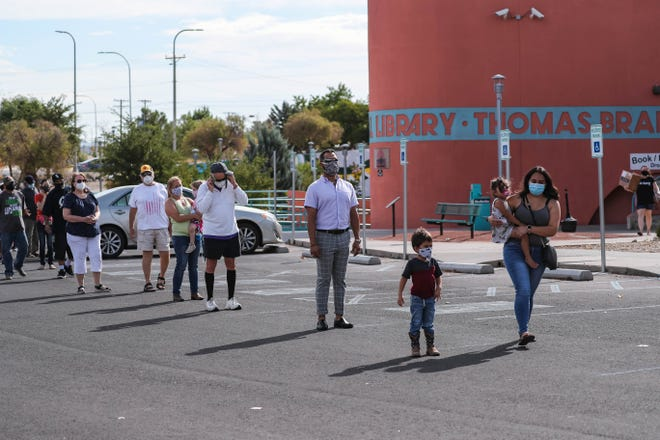 People wait in line at a free face mask and sanitation kit giveaway event at the parking lot of Thomas Branigan Memorial Library in Las Cruces on Saturday, July 18, 2020.