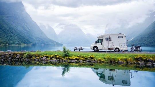 Un RV estacionado frente a un pintoresco lago en un parque.